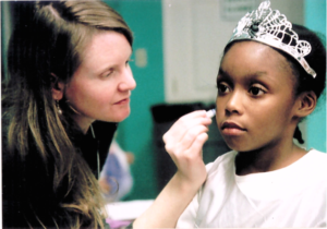 A woman paints the face of a little girl wearing a tiara.