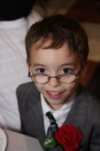 A little boy with glasses and a suit smiles at the camera.