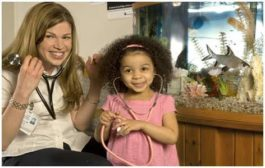 A woman and a little girl play with stethoscopes in front of a fish tank.